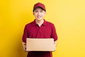 Portrait de livreur asiatique, isolé sur fond jaune photo