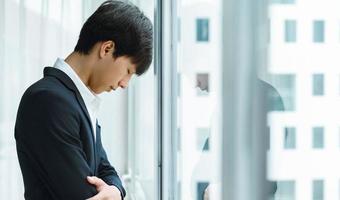 jeune homme d'affaires fatigué se reposant la tête par la fenêtre photo