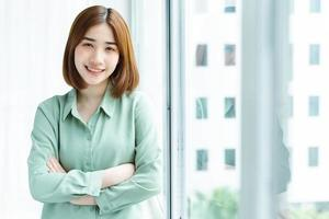 portrait de jeune femme d'affaires debout près de la fenêtre de l'entreprise photo