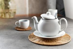tasse à thé et théière en porcelaine blanche, décor de table à thé l'après-midi photo