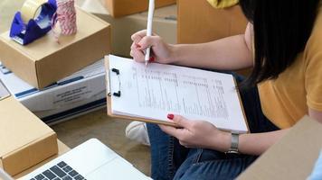 la femme vérifie les fichiers de stock pour l'expédition aux clients. photo