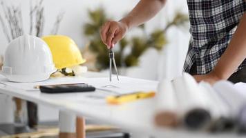 la main de l'homme utilise un rond-point pour écrire sur un plan de maison. photo