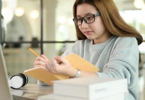 une étudiante adolescente portant des lunettes étudie en ligne à partir d'un ordinateur portable. photo