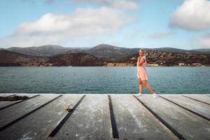 femme blonde en robe blanche à rayures rouges debout sur le quai du navire au coucher du soleil, souriant et regardant la caméra. concept de tourisme. argostoli, céphalonie, grèce. photo