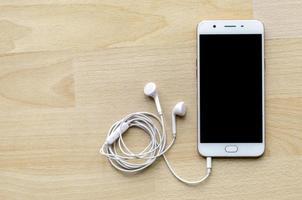 Smartphone à écran blanc avec écouteur sur le coin supérieur de la table en bois photo