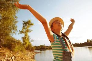petite fille heureuse dans un chapeau à bras ouverts photo