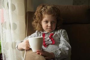 petite fille réfléchie avec une tasse photo