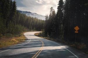 voyage sur la route avec la lumière du soleil à travers la forêt au parc national banff photo