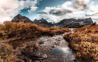 Mont Assiniboine avec ruisseau qui coule dans la forêt d'automne au parc provincial photo