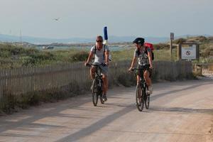 Les touristes à vélo sur la plage des illetes à Formentera en Espagne 2019 photo