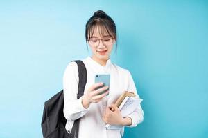portrait d'une belle écolière sur fond bleu photo
