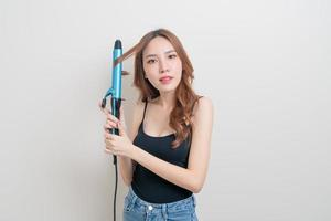 Portrait belle femme asiatique à l'aide d'un bigoudi ou d'un fer à friser photo