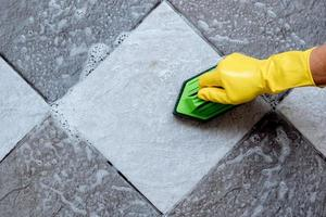 nettoyer le sol carrelé avec une brosse à sol en plastique de couleur verte. photo