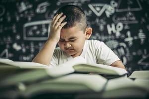 les garçons avec des lunettes écrivent des livres et réfléchissent en classe photo