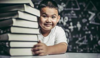 un garçon étreignant une pile de livres. photo
