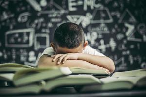 un garçon avec des lunettes étudiant et somnolent. photo
