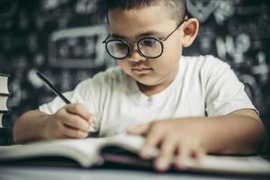 un garçon avec des lunettes homme écrit dans la salle de classe photo