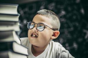 un garçon avec des lunettes assis dans la classe en comptant les livres photo