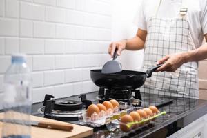 un chef asiatique a fait frire des œufs sur une poêle à de la nourriture thaïlandaise dans une cuisine sur une cuisinière à gaz l'huile dans une poêle bouillante. des œufs et du porc cuits. avant de servir à une famille heureuse pour manger ensemble à la maison photo
