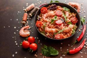 pâtes savoureuses aux crevettes et tomates sur une poêle à frire photo