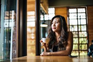 portrait, femme asiatique, sourire, se détendre, dans, café-restaurant, café photo