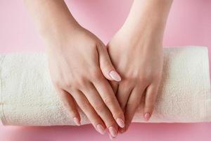 procédure de spa pour le soin des ongles dans un salon de beauté. mains féminines et outils de manucure sur fond rose. concept de soins du corps. photo