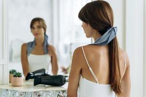 portrait de jeune fille sortante avec une nouvelle coiffure en regardant le miroir à l'intérieur. souriante jeune femme faisant la coiffure devant le miroir dans la salle de bain. stock photo