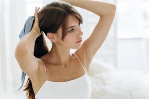 jolie femme se brosser les longs cheveux bruns dans la salle de bain le matin le tenant dans une main en queue de cheval alors qu'elle se prépare à attacher un arc photo