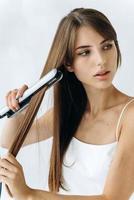 vue verticale d'une belle jeune femme caucasienne gaie en train de repasser à chaud ses cheveux à la maison tout en détournant les yeux et en pensant à quelque chose photo