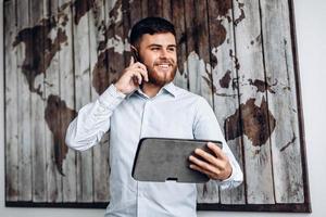 bel homme d'affaires occupé parlant au téléphone et regardant un document important sur une tablette. photo