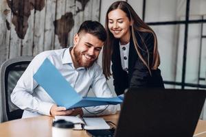 un directeur souriant et son assistant travaillent au bureau photo