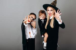 famille déguisée montrant un geste effrayant en regardant la caméra.- image photo
