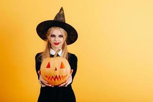 femme debout sur un fond jaune tenant une citrouille et la montrant sur les mains droites photo