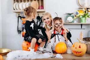 joyeux préparatifs de famille à Halloween. garçon montrant la langue et femme souriant photo