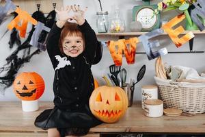 petite fille assise à côté de la citrouille et montrant un bras sale en regardant la caméra. - concept d'halloween photo