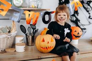 petite fille assise à côté de la citrouille et montrant un geste effrayant. - concept d'halloween photo