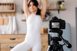 jeune blogueuse enregistrant une vidéo de sport à la maison photo