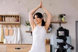 belle jeune femme faisant du yoga et filmant une vidéo photo