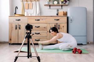 jolie jeune femme souriante filmant une vidéo sur son entraînement sportif photo