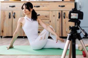 jeune blogueuse séduisante souriante et s'étirant assise sur le tapis et réalisant une vidéo pour son blog photo