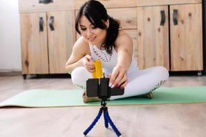 jeune femme portant des vêtements de sport blancs faisant du yoga assis en position du lotus, tourne une vidéo photo