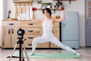 la formation en ligne. joyeuse jeune femme faisant des exercices tout en enregistrant une vidéo d'une formation photo