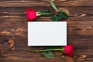 roses rouges et feuille de papier vierge sur planche de bois, fond de la Saint-Valentin, jour du mariage photo