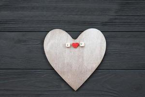 coeur en bois se trouve sur fond en bois. concept d'événements d'amour, saint valentin photo