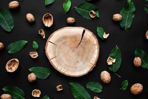 coquille de noix et feuilles vertes fraîches dispersées sur un fond noir. coupe d'arbre en bois au centre photo