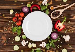 sur une table en bois se trouve une assiette, entourée de produits italiens et d'épices photo