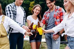 Image en gros plan d'une entreprise d'amis soulevant une bouteille avec une bière dans le camping photo