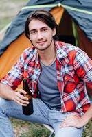 un gars assis à côté de la tente avec une bouteille de bière et souriant en regardant la caméra photo