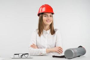 femme souriante est assise à la table dans un casque orange croisa les bras photo