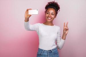 Jeune fille tenant un téléphone portable prend une photo avec un geste de victoire selfies - image